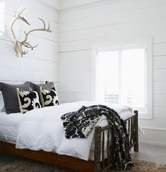 High-Contrast Cottage Bedroom Painted, rough-cut pine panels offer rustic charm.