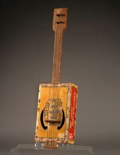 A four stringed banjo/ukelele certain to talk to any musician collector of American folk art. Hand carved neck and pegs connect to a cigar box body/resonator with two clef soundholes. A wonderful survivor/artifact from about 1900.