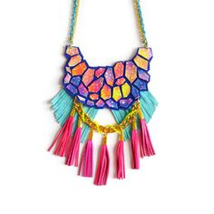 This colorful statement necklace features a hand painted nebula galaxy pattern on leather combined with neon fringe and woven chain details. I