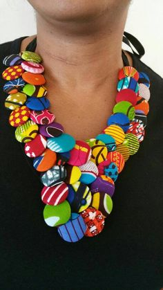 Handmade Chunky multi colours button necklace made with different types of African Print fabric. Over thirty five fabric covered beads of excellent quality are hand sewn on a black velour base fabric and it finished with ribbons used to adjust the length as you tie at the back. They look absolutely beautiful and makes a statement with any type of plain attire.  Please note that these Necklace sets are made from various fabrics so you may not necessarily receive the exact fabric designs as…