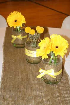 Centerpieces of 3 mason jars wrapped with burlap and ribbon.  Gerbera daisies and Craspedia flowers!
