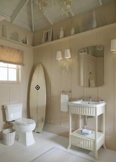 une salle de bain blanche avec une planche de surf et des étoiles de mer
