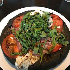 Caprese Pizza - black carbon bread basil pesto mozzarella tomato prosciutto arugula balsamic reduction - Mangia.  Perfect!