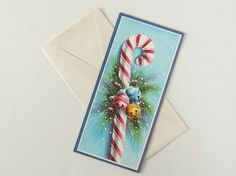 Traditional red and white candy cane has colorful jingle bells and pine decorations on this vintage blue Christmas holiday card. An unused card
