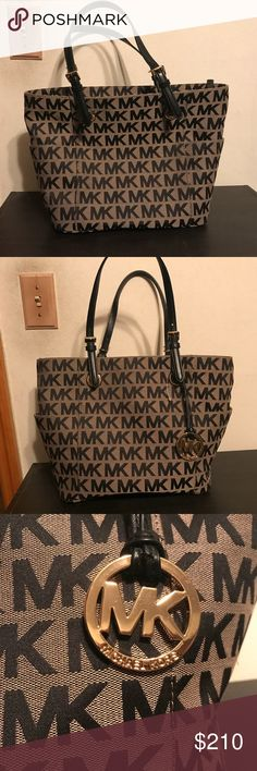 Michael Kors signature MK bag NWOT  Tan w/ black text and black inside  2 pockets outside  1 large dividing pocket inside (middle) w/ zipper 4 smaller pockets  1 zipper pocket on inside side of bag.  Gold accents (metal/buckles/zippers)  Used for one day, but still has the plastic from tag on bag. Michael Kors Bags Shoulder Bags