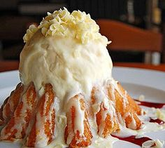 WHITE CHOCOLATE MOLTEN CAKE   This cake is topped with vanilla ice cream, inside a crunchy white chocolate shell and seasoned with white chocolate curls and raspberry sauce.