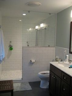 white subway tile bathroom with pebble flooring | What a gorgeous bathroom! White subway tile, dark flooring and vanity ...