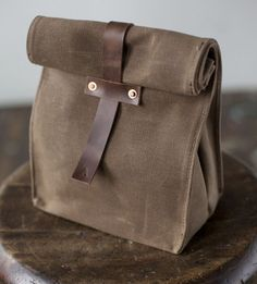 No. 215 tote from the Artifact Bag Co. It is made of waxed canvas, rolls down at the top like a paper bag, and fastens with leather straps and copper rivets.