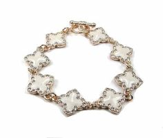 FASHION DESIGNER INSPIRED GOLD WHITE CLOVER SHAPE BRACELET Troy Designs. $20.30. TOGGLE BRACELET. 100% SATISFACTION. COLOR: GOLD WITH WHITE. LENGTH: 7.5 INCHES