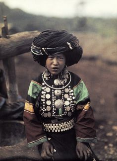 A Lissu child poses in a large turban and decorative silver pendents.