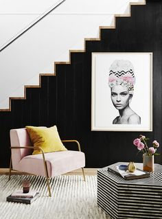 Mod living space with a staircase doubling as a black contrast wall, pop art, and a blush armchair