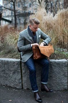 Shop this look on Lookastic:  http://lookastic.com/men/looks/scarf-chelsea-boots-jeans-messenger-bag-blazer-tie-pocket-square/8006  — Charcoal Scarf  — Dark Brown Leather Chelsea Boots  — Navy Jeans  — Brown Leather Messenger Bag  — Grey Wool Blazer  — Dark Brown Tie  — White Pocket Square