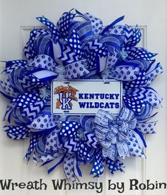 University of Kentucky Wildcats Sports Wreath.   Show your team spirit with this University of Kentucky Wildcats deco mesh wreath!  This wreath is constructed with premium deco mesh in a blue/white stripe. Surrounding the wreath are 34 ribbon streamers all in your teams colors. An officially licensed UK license plate sits front and center. Finishing off the look is a bow made with Kentucky print ribbon.  This wreath measures approximately 28 inches. Go Cats!   * I do NOT make money on…