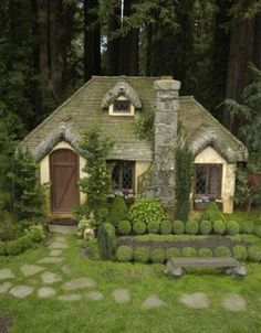 This little cottage almost looks too perfect to be real. Its setting, just against the dark woods, contrasts with its picture-perfect topiaries and welcoming steps.
