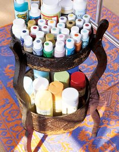 A vintage double-decker table holds some basic crafts paints and adhesives, keeping bottles and cans upright. Koko Co.'s easy-clean plastic mat lends spill coverage to Carpet One's stain-resistant broadloom.    Read more: Craft Room Ideas and Designs - Craft Room Organization Ideas - Country Living