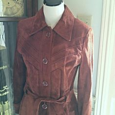 VINTAGE Beautiful Rust Suede Full Length Coat This vintage suede coat is fantastic. It is in great condition. The discoloration in the first picture is just lighting. Great detailed stitching across the bodice and a tailored cut makes it look super sexy on. Matching belt, finished cuffs and side pockets are some of the great details. Full length, heavy and warm with a full lining with no stains or rips. It is a vintage 13/14 and as such runs small. Fits more like a 9/10. Too tight for me and…