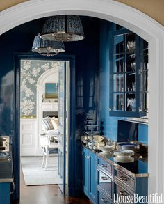 The butler's pantry, which connects the dining room to the kitchen, is lacquered in a custom blue. The Charles Edwards pendant lights have shades made of Fortuny's Solimena.