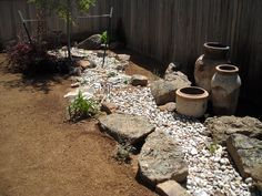 Dry creek bed with cool planters as an off-center, center piece. Moss rock for anchors and accents.