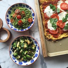 Healthy homemade brunch consisting of zucchini pasta with pesto brussels sprouts and cauliflower crust pizza with @zavong and @sai_phat  by ediblemoments