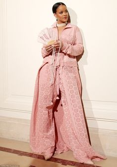 An eye for design: Wearing a long, floor-length pink trenchcoat, which featured a printed design, the singer cut a chic but modest figure