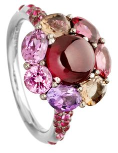 Theroom Rhodolite Garnet Cocktail Ring in 18k white gold with coloured gemstones by Astley Clarke. The floral design features a cabochon of deep-red rhodolite, which has been shaped and polished rather than faceted to give it its distinctive, orb-like glow. Encircled by petals of faceted precious stones - a pair of quartz, an amethyst, a pink sapphire, a pink tourmaline, a purple sapphire and a ruby - the jewelladen flower sits on a half-band of pave ruby and pink sapphires.
