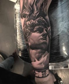 Black and grey Michelangelo's David tattoo on the forearm.