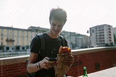 Young man eating pizza and using mobile phone by Davide Illini for Stocksy United