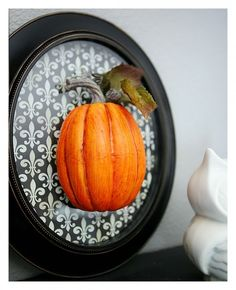 Cut a styrofoam pumpkin in half and glue to glass.  Could eliminate the glass and glue to the paper, no?