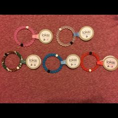 5 Small Lokai Bracelets! 5 Colors Hi, you're looking at one small 5 stack of Lokai bracelets: blue, pink, Camo, red, clear. They come new with tags, never used. I purchased these from a chain of boutiques closing in my area, so I cannot personally verify they are authentic. I cut them open and compared them to real ones and they seem real enough. Still, I don't have the papers so BUY AT YOUR OWN RISK! ***ONCE AGAIN, BEWARE, THIS IS CANNOT BE CONFIRMED AUTHENTIC!*** I am selling them cheap…