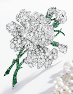 Platinum, diamond and emerald brooch, Charlton & Co. Photo Sotheby's  ~  Designed as a peony blossom centered by an old European-cut diamond weighing approximately .90 carat, accented by numerous round, old European and single-cut diamonds weighing approximately 15.00 carats, the stems set with calibré-cut emeralds, signed Charlton; circa 1935.