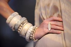 A large stack of Monique Pean bracelets made from fossilized Wooly Mammoth ivory.