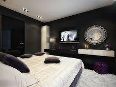 Black & White glamorous bedroom. Shag rug. Purple ottoman. Black walls.