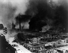 German soldier and a civilian observing fires ravaging Fieseler aircraft plant at Bettenhausen, a suburb of Kassel, Germany, after bombing by R.A.F. and the U.S. Eighth Air Force. Read more: http://histomil.com/viewtopic.php?f=338&t=3918&start=1340#ixzz3ShZ5XgQg