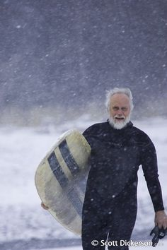 Photo - John Langham carrying his surfboard through a heavy snowfall on a snowy beach making his way to the surf in winter in Alaska. (MR)