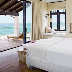 Sliding glass doors provide an unobstructed view from this master suite to the blue-green water outside. | Coastalliving.com
