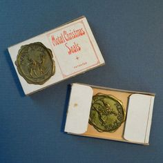 This is a vintage box of gold colored metal Christmas seals made in the USA.
