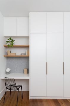 Tiny, simple office nook in white with open blonde wood shelves and felt tack board