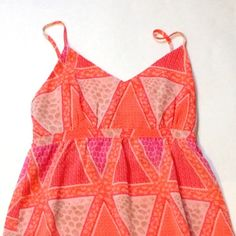 Old Navy Dress Never worn! Beautiful orange and pink colors with adjustable straps. It is lined so you cannot see through it. 100% polyester and machine washable. From the top of the strap to the bottom is approx 36 1/2 inches.  Offers are always welcome but I do not trade. Old Navy Dresses