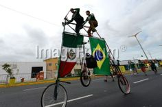 BRAZIL, Fortaleza : Fans arrive on a tandem bicycle for a Group A football match between Brazil and Mexico in the Castelao Stadium in Fortaleza during the 2014 FIFA World Cup on June 17, 2014. AFP PHOTO / VANDERLEI ALMEIDA