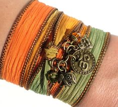 This listing is for one Om silk wrap bracelet. It can also be used as a necklace or anklet. It features a hand dyed earth tone silk ribbon, antique brass Buddha charm, a Sacred Elephant charm, a Om charm, and swarovski crystals. Just wrap it around your wrist, upper arm, or