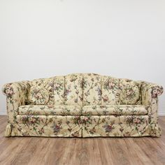 This sofa is upholstered in a durable off white beige, pink and green floral liberty chintz print fabric. This long sofa is in great condition with a curved channel back, a ruffled skirt and accent pillows. Country chic couch perfect for long naps! #country #sofas #sofaorcouch #sandiegovintage #vintagefurniture