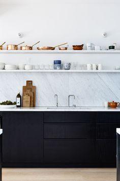 Zwarte keuken met wit blad, marmeren achterwand en zwevende marmeren planken