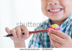 Smiling boy use a pencil sharpener and Rainbow pencil  shaving ,Creative concept,  - stock photo