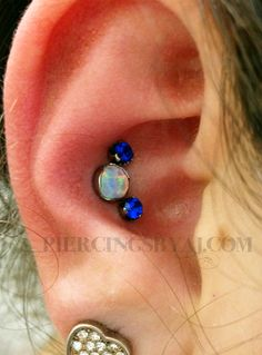 I will never get tired of doing triple conches! This set features a 14g 5mm prong set white opal and two 16g 3mm prong set saphire gems, all jewelry from Anatometal!