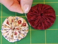 Learn how to join the fabric yo-yos to make a doily the size you want with these instructions. The goal of joining yo-yos is seamless unions.: Attaching Yo-Yos -- Step 3