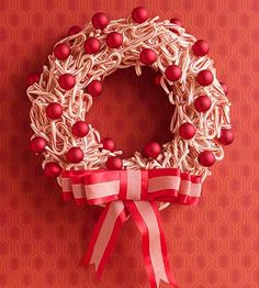 How to Make Christmas Wreaths | DIY Wreaths -- This lovely wreath is a creative use for all those beautiful candy canes available during the holidays. Using a hot-glue gun, randomly glue candy canes to a foam wreath form. When finished, glue some red ornaments and a striped bow to finish the decoration.