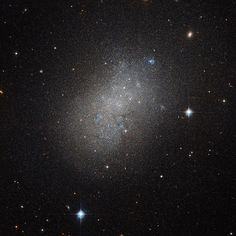 Irregular Island in a Sea of Space: This image, courtesy of the Hubble Space Telescope, captures the glow of distant stars within a dwarf galaxy located just over 15 million light-years away in the constellation of Hydra (The Sea Serpent). Dwarf galaxies like this typically possess around a billion stars - just 1 percent of the number of stars found within the Milky Way. They are usually found orbiting other larger galaxies such as our own, and are thought to form from the material left…