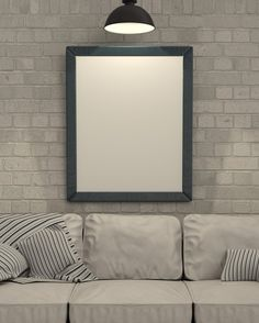 blank white framed on brick wall behind couch, white and neutral tones