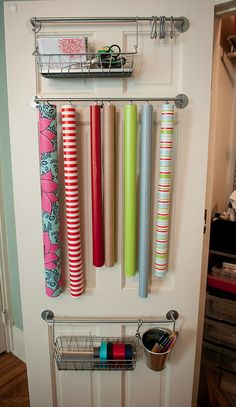 Storing gift wrap: Mount an IKEA towel bar on the back of the door. Clip wrapping paper rolls with curtain clips and hang from towel bar.