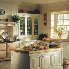 color of kitchen cupboards, like the plants scattered around, three small frames and glass window cupboards.  Also remember antique clock